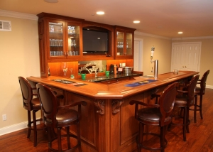 Features a wet bar with lower granite tops and a built-in beer tap in a solid cherry hardwood bar top, this custom bar was designed to fit in a designated area of a newly finished and remodeled basement for the client.