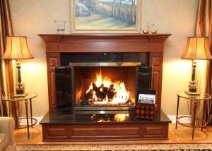 This cherry fireplace treatment with granite hearth was designed to replace an existing older fireplace treatment.