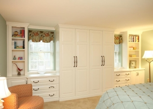 This custom built in wall treatment was designed to replace closets on the back wall of the bedroom. The center section between the windows features a combination of double and single hanging closet rods.